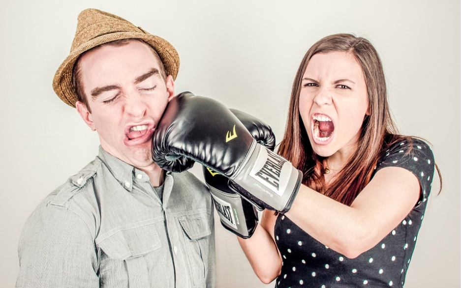 woman punching a man int he face with a boxing glove to illustrate small businesses punching above their weight
