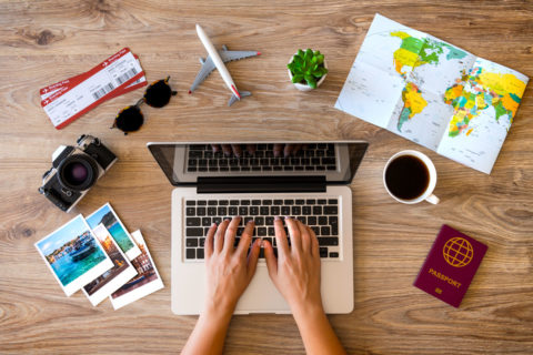laptop surrounded by travel items such as a map, model aeroplane, and passport to illustrate the biggest seo mistakes bloggers make