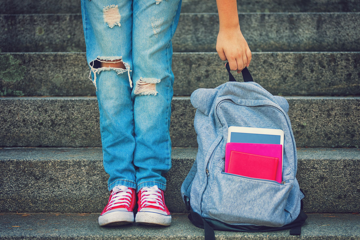 child wearing ripped jeans and red lace ups with a blue rucksack containing books to illustrate back to school