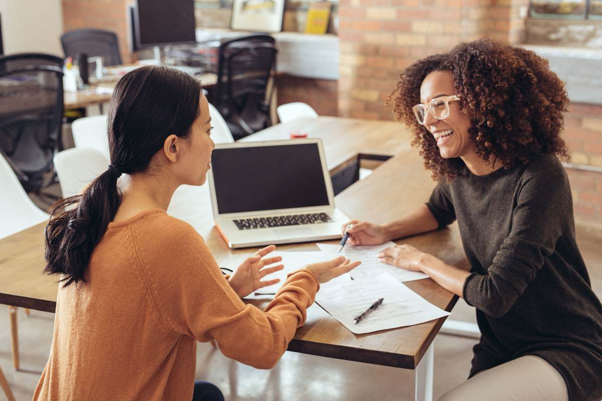 two women with a laptop discussing how to set realistic expectations for seo