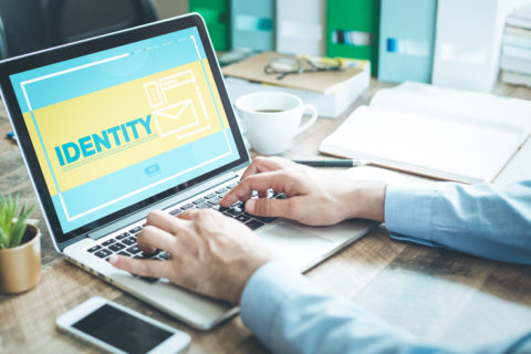 man typing on laptop showing identity screen