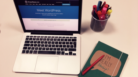 laptop with wordpress website, pen of full of pens and notepad