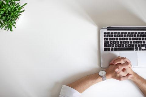 hands praying next to laptop