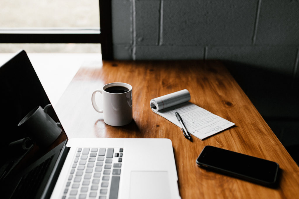laptop, smartphone, coffee and notepad on wooden desk