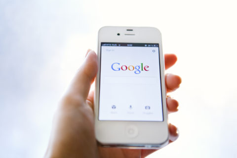 hand holding a smartphone with google search screen
