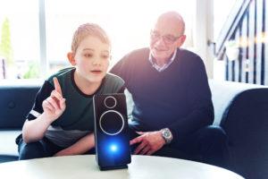 young boy asks digital assistant a question