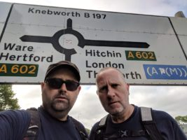 Stuart and Ian next to a sign showing Knebworth, Hertford, and Hitchin