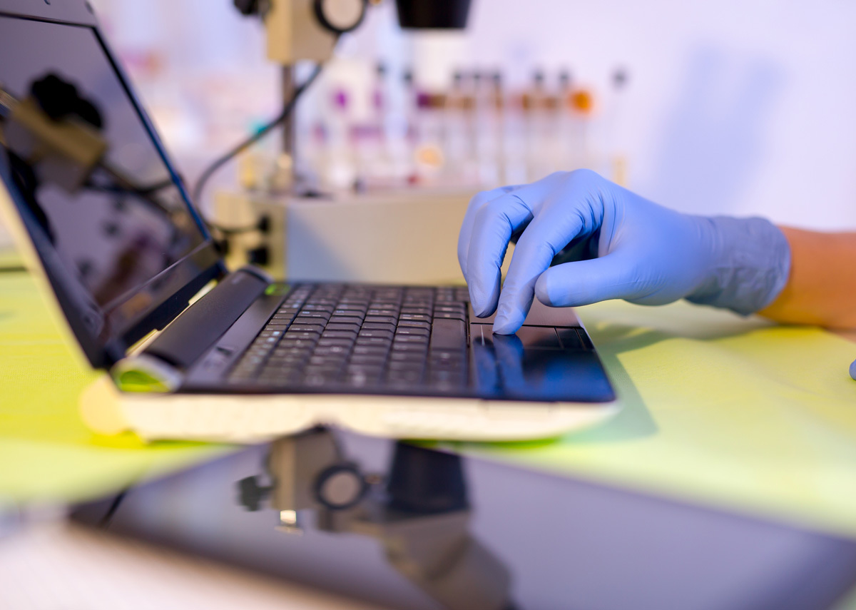 a hand with a plastic glove on typing on a laptop in a life science lab